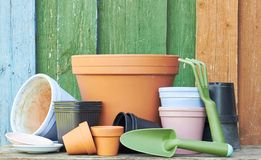 Free Terracotta Clay Flower Pots With Black Plastic Containers And Garden Tools On Wooden Table Stock Images - 167551394