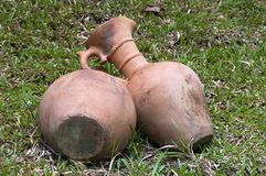 Terracotta ewers or jugs laying on lawn royalty free stock photos