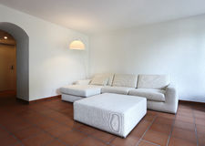 Terracotta floors and white sofa Stock Image