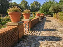 Terracotta flower pots arrayed on brick wall in Parc de Bercy, Paris, France. Terracotta flower pots are arrayed along a brick wall in the Parc de Bercy in the Royalty Free Stock Photography