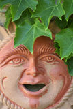Terracotta sunshine man. Terracotta garden sculpture of smiling sunshine person with overhanging green leaves stock photos