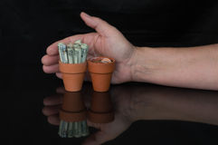 Terracottapot met opgerold geld, verandering en hand achter het Royalty-vrije Stock Foto
