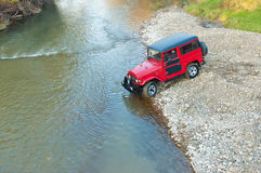 Terrain car passes by the river Royalty Free Stock Photo