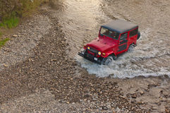 Terrain car passes by the river Royalty Free Stock Image