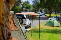 Terrain de camping avec des tentes, des voitures et des arbres dans l'Australie Photographie stock