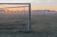 Terrain de football abandonné et vieux buts rouillés sur le coucher du soleil Images libres de droits