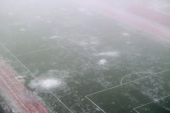Terrain de football dans le brouillard et la neige de fonte Image stock