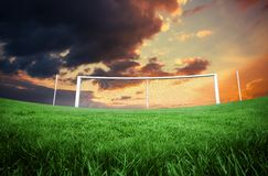 Terrain de football sous le ciel orange nuageux Image stock