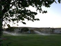 Terrain de golf avec des arroseuses Photo stock