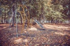 Terrain de jeu abandonné en parc d'automne Images libres de droits