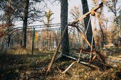 Terrain de jeu abandonné rampant d'enfants parmi des arbres d'automne, oscillation rouillée image libre de droits