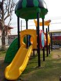 Terrain de jeu coloré de glisseur jaune pendant des temps d'enfant de bonheur Photos libres de droits
