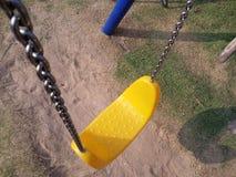 Terrain de jeu coloré d'oscillations de jaune pendant des temps d'enfant de bonheur Photo stock