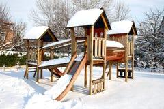 Terrain de jeu d'enfants en parc public couvert de neige d'hiver Photographie stock libre de droits