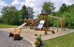 Terrain de jeu du ` s d'enfants couvert de sable avec une glissière pour une oscillation avec un banc en bois de position de plat Photos stock