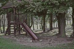 Terrain de jeu extérieur d'aventure pour des enfants Équipement en bois de terrain de jeu avec des glissières au printemps image libre de droits