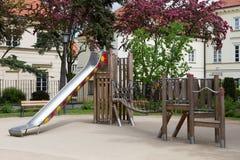Terrain de jeu moderne en bois et en métal avec le glisseur et le pont de secousse pour des enfants Photo stock