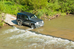 Terrain vehicle crosses the stream Royalty Free Stock Photography