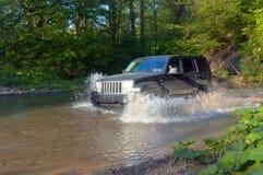 Terrain vehicle crosses the stream Stock Photography