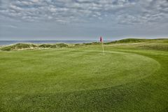 Terrains de golf fonctionnant le long de la mer images stock