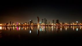 terraplén Orilla del mar de la opinión de la noche de la ciudad con los rascacielos y foto de archivo libre de regalías