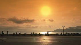Terraplén y cuadrado central en la opinión del mar de Nha Trang Vietnam Puesta del sol con el sol en colores amarillos almacen de metraje de vídeo