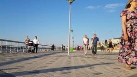 Terraplenagem aglomerada em um dia de verão em Nizhny Novgorod Os adultos, famílias com crianças andam no verão pelo rio filme