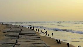 Terraplenagem concreta com as colunas de madeira velhas que colam fora da areia amarela na perspectiva das ondas de oceano sob um video estoque