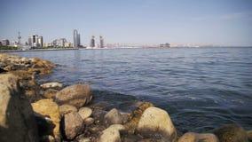 Terraplenagem de Baku, Azerbaijão O mar Cáspio, as pedras e os arranha-céus Movimento lento vídeos de arquivo