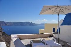 Terras en ligstoelen op de Caldera van Santorini-Eiland Griekenland stock afbeelding