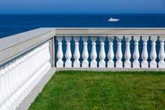 Terras met groen gazon en steentraliewerk met balustrades royalty-vrije stock afbeelding