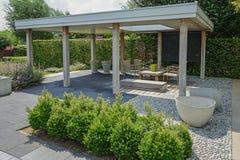 Tuin met modern tuinmeubilair en in vijver redactionele afbeelding