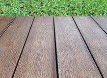 Terras van de close-up het lege uitstekende bruine houten bevloering met groen grasgebied Royalty-vrije Stock Fotografie