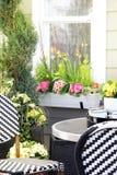 Terrasmeubilair door de lentebloemen die wordt omringd Royalty-vrije Stock Afbeelding