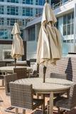 Terrasmeubilair met gevouwen paraplu's stock afbeelding