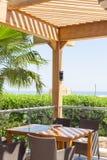 Terrass av restaurangen som förbiser havet och palmträden Arkivbild