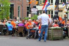 Terrass med folk och holländsk flagga på Kingsday Royaltyfria Foton