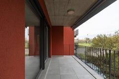 Terrass som förbiser naturen av lägenheten med röda yttre väggar arkivbilder