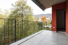 Terrass som förbiser naturen av lägenheten med röda yttre väggar arkivfoton