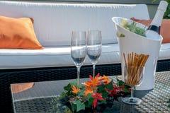 Terrasse avec les verres de champagne et la bouteille de champagne dans le refroidisseur Photographie stock libre de droits