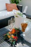 Terrasse avec les verres de champagne et la bouteille de champagne dans le refroidisseur Image libre de droits