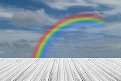 Terrasse en bois et ciel bleu avec l'arc-en-ciel Photo stock