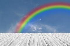 Terrasse en bois et ciel bleu avec l'arc-en-ciel Image stock