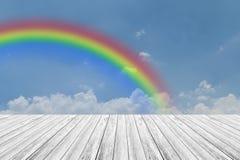 Terrasse en bois et ciel bleu avec l'arc-en-ciel Photographie stock libre de droits