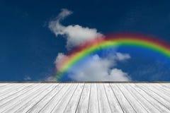 Terrasse en bois et ciel bleu avec l'arc-en-ciel Image libre de droits
