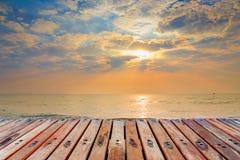 Terrasse en bois sur la plage avec le fond de coucher du soleil Photos stock