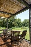 Terrasse mit hölzerner Tabelle und Stühlen Lizenzfreie Stockfotos
