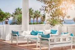 Terrasse mit Spalten, weiße Bänke mit blauen Kissen durch das Meer und die Palmengassen an einem sonnigen Tag Lizenzfreie Stockfotos