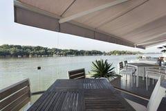 Terrasse moderne de café de rive pendant le matin images stock
