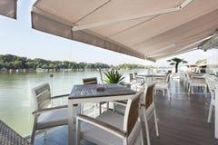 Terrasse moderne de café de rive pendant le matin photographie stock